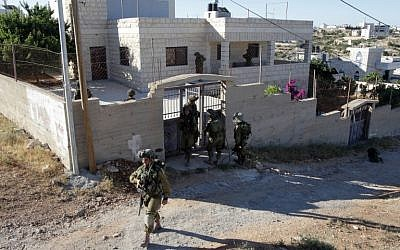 Israeli soldiers inspect a house in the West Bank village of Tafoh, near Hebron on June 15, 2014, as they search for three teenagers who went missing near a West Bank settlement. (photo credit: AFP/ HAZEM BADER)