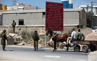Israeli soldiers man a checkpoint in the West Bank city of Hebron on Sunday, June 15, 2014, as Israel broadened the search for three teenagers believed kidnapped by terrorists (photo credit: AFP/MENAHEM KAHANA)