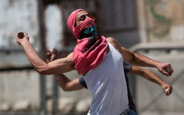 Palestinians throw stones at Israeli forces (unseen) during clashes in the center of the West Bank town of Hebron on June 16, 2014. (photo credit: Menahem Kahana/AFP)