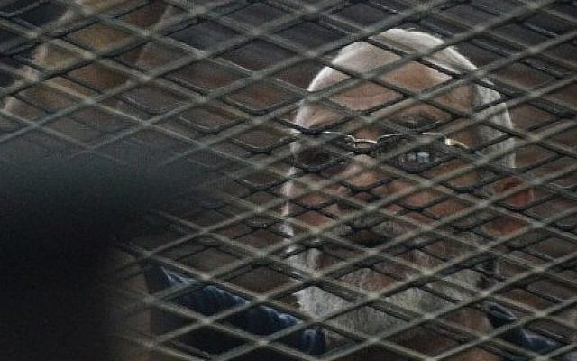 Egyptian Muslim Brotherhood leader Mohammed Badie stands behind the defendants cage during his trial on June 18, 2014 (Photo credit: Mohammed el-Shahed/AFP)