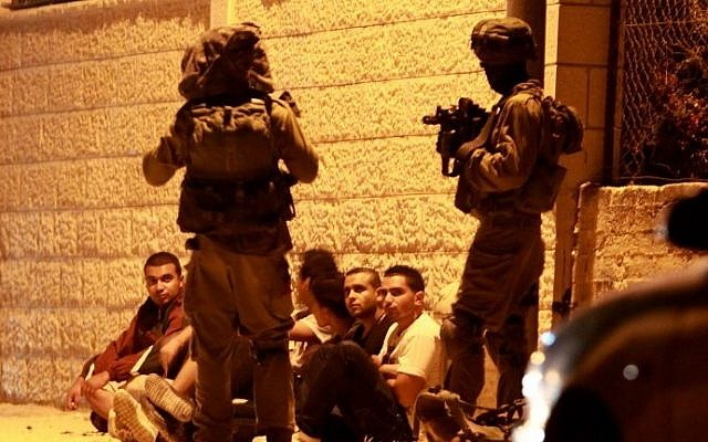 Israeli security forces detain Palestinian men early on June 22, 2014 in the West Bank village of Beit Sahur during an operation to locate the three teenagers they  abducted by Islamist movement Hamas on June 12. (photo credit: AFP/Musa al Shaer)