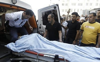 Paramedics arriving at a hospital carry the body of Ahmed Fahnawi, a 27-year-old Palestinian man who was shot and killed on his way to a mosque for morning prayers as clashes with Israeli troops were taking place in Nablus on Sunday, June 22, 2014 (photo credit: AFP/JAAFAR ASHTIYEH)