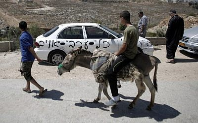 """A Palestinian man rides his donkey past one of ten cars that were sprayed with racist slogans that read in Hebrew """"All the Arabs are enemies"""" in the east Jerusalem neighborhood of Beit Hanina on June 23, 2014. (photo credit: Ahmad Gharabli/AFP)"""