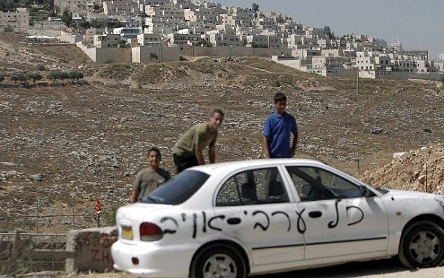 "Palestinians stand next to one of ten cars that were sprayed with racist slogans that read in Hebrew ""All the Arabs are enemies"" in the east Jerusalem neighborhood of Beit Hanina, next to the Jewish settlement of Ramat Shlomo (background), on June 23, 2014. (photo credit: Ahmad Gharabli/AFP)"