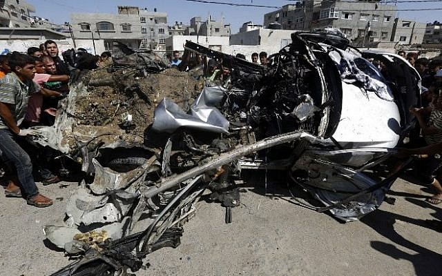 Palestinians gather around a car that was targeted by an Israeli air strike in Gaza City on June 27, 2014. (Photo credit: AFP/ MOHAMMED ABED)