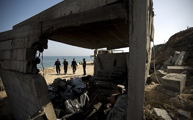 Palestinian security personnel inspect a damaged building following overnight Israeli air raids in the central Gaza Strip on June 28, 2014. (photo credit: AFP PHOTO/MAHMUD HAMS)