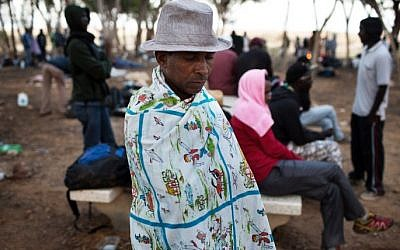 An African asylum seeker sits in a makeshift outdoor camp near Israel's Nitzana border crossing with Egypt on June 28, 2014. (photo credit: AFP/MENAHEM KAHANA)