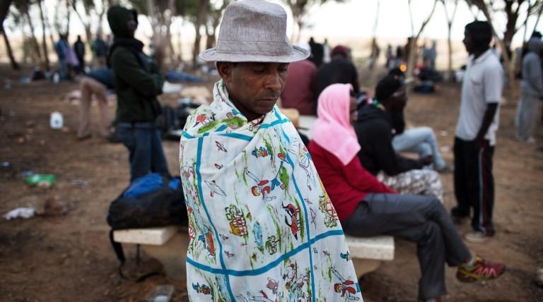 An African asylum seeker sits in a makeshift outdoor camp near Israel's Nitzana border crossing with Egypt on June 28, 2014. (photo credit: AFP/MENAHEM KAHANA)
