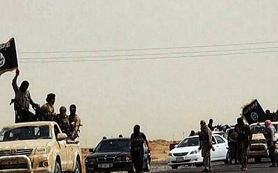 An image uploaded on June 14, 2014 on the jihadist website Welayat Salahuddin allegedly shows militants of the Islamic State of Iraq and the Levant (ISIL) driving on a street at unknown location in the Salaheddin province. (photo credit: AFP PHOTO / HO / WELAYAT SALAHUDDIN)