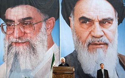 Iranian President Hassan Rouhani delivers a speech under portraits of Iran's supreme leader, Ayatollah Ali Khamenei (left) and Iran's founder of the Islamic Republic, Ayatollah Ruhollah Khomeini (right), on the eve of the 25th anniversary of the Islamic revolutionary leader Ayatollah Ruhollah Khomeini's death on June 3, 2014 (Photo credit: Atta Kenare/AFP)