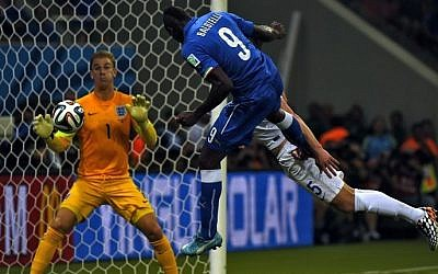 Italy's forward Mario Balotelli (C) heads the ball to score a goal as England's goalkeeper Joe Hart (L) and England's defender Gary Cahill try to defend during a Group D soccer match between England and Italy at the Amazonia Arena in Manaus during the 2014 FIFA World Cup on June 14, 2014 (photo credit: AFP/FABRICE COFFRINI)