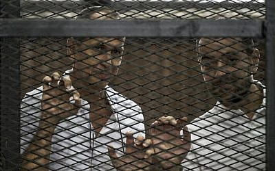 Al-Jazeera channel's Australian journalist Peter Greste (left) and Egyptian journalist Mohamed Baher stand inside the defendants cage during their trial for allegedly supporting the Muslim Brotherhood at the police institute near Cairo's Tora prison on June 1, 2014. (photo credit: AFP/Khaled Desouki)