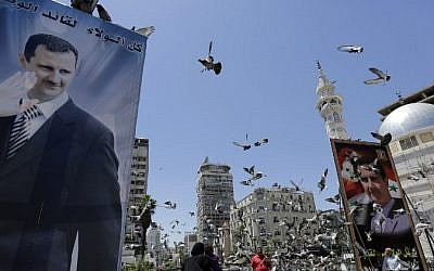 Syrians feed pigeons on a square where are displayed giant campaign billboards bearing portraits of Syrian President Bashar Assad on June 1, 2014 in the capital Damascus. (Photo credit: AFP/Joseph Eid)