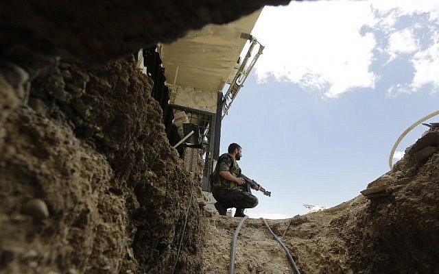 A Syrian army soldier secures the entrance of a tunnel reportedly dug by rebels fighters in Jobar, a mostly rebel-held area on the eastern outskirts of Damascus, on June 2, 2014. (photo credit: AFP/Joseph Eid)