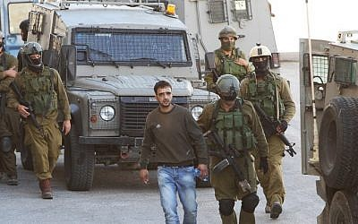 Israeli soldiers detain a Palestinian man in the West Bank city of Hebron on June 14, 2014, as they search for three teenagers who went missing near Gush Etzion (Phot credit: Hazem Bader/AFP)