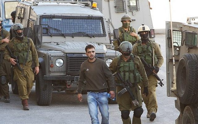 Israeli soldiers detain a Palestinian man in the West Bank town of Hebron on June 14, 2014, as they search for three teenagers who went missing near Gush Etzion (Phot credit: Hazem Bader/AFP)
