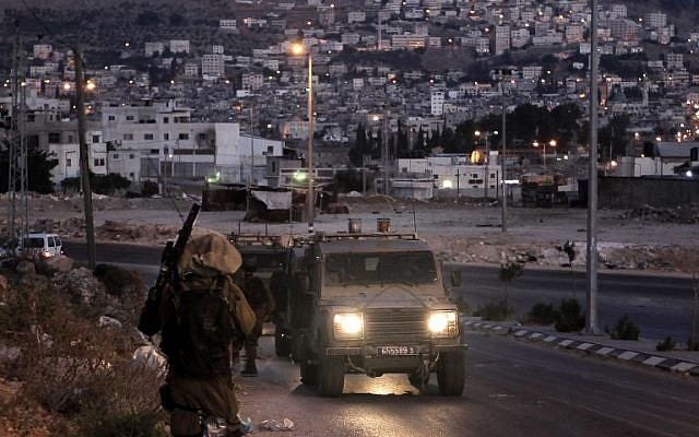 Israeli soldiers take part in a search operation for three Israeli teenagers believed kidnapped by Palestinian militants, early on June 18, 2014 in the West Bank town of Nablus. (photo credit: AFP/Jaafar Ashtiyeh)