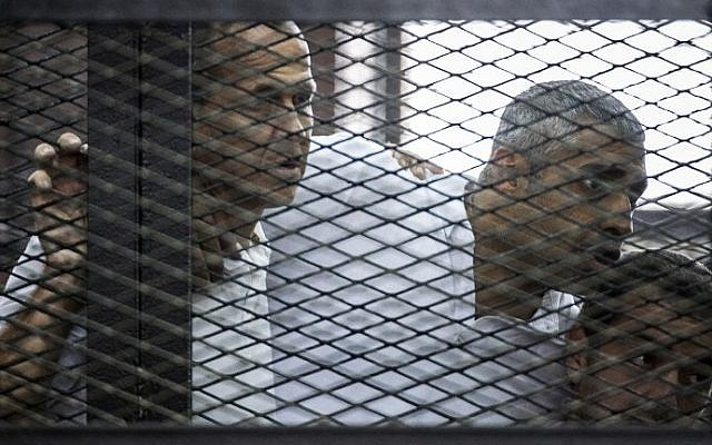 Al-Jazeera news channel's Australian journalist Peter Greste (L) and his colleagues, Egyptian-Canadian Mohamed Fadel Fahmy (C) and Egyptian Baher Mohamed , listen to the verdict inside the defendants cage during their trial for allegedly supporting the Muslim Brotherhood on June 23, 2014 at the police institute near Cairo's Tora prison. (photo credit: AFP Photo/Khaled Desouki)