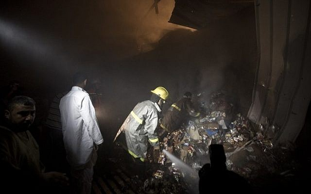 Palestinians and firemen inspect a food store following an air strike by the Israeli Air Force on Gaza City on June 20, 2014. (photo credit: Mahmud Hams/AFP)