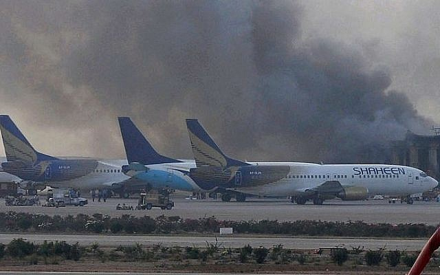 Smoke rises after militants launched an early morning assault at Jinnah International Airport in Karachi on June 9, 2014. Pakistan's security forces said they have relaunched a military operation at Karachi airport as gunfire resumed several hours after they announced the end of a militant siege that left 24 dead. (photo credit: AFP/Rizwan Tabassum)