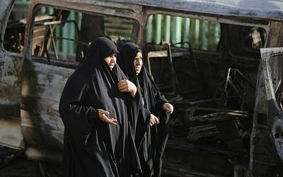 Iraqi women walk at the site of a car bomb explosion in the mainly Shiite Sadr City district in Baghdad on June 18, 2014 which killed at least seven people and wounded 20. The blast came amid a week-long militant offensive in which insurgents have seized vast swathes of territory in northern Iraq. (photo credit: AFP/Ahmad al-Rubaye)