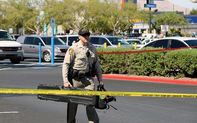 A Las Vegas Metropolitan Police Department officer removes equipment from a Wal-Mart on June 8, 2014 in Las Vegas, Nevada. Two officers were reported shot and killed by two assailants at a pizza restaurant near the Wal-Mart. The two suspects then reportedly went into the Wal-Mart where they killed a third person before killing themselves. (photo credit: Ethan Miller/Getty Images/AFP)