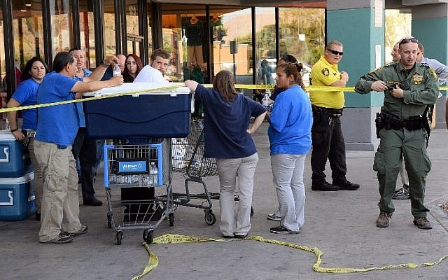 Las Vegas Metropolitan Police Department officers stand near Wal-Mart employees near their store on June 8, 2014 in Las Vegas, Nevada. (Photo credit: Ethan Miller/Getty Images/AFP)
