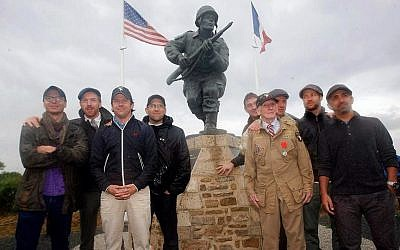 "Damian Lewis (second from left), Ben Caplan (fourth from left) and other ""Band of Brother"" actors posed with WWII veteran JIm 'Pee Wee' Martin at Major Dick Winters statue in Normandy. (Courtesy)"