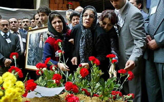 Nermin Sahin, center, whose son Murat was killed following a suicide attack at an Istanbul synagogue, lays flowers at the scene of the blast in Istanbul, November 15, 2004 [photo credit: Osman Orsal/AP]