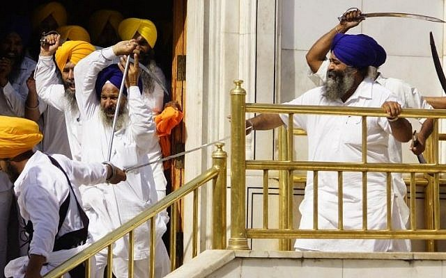 Members of a hardline Sikh group clash with guards of the Sikh's holiest shrine, the Golden Temple, in Amritsar, India, Friday, June 6, 2014. Half a dozen people were wounded Friday as members of a Sikh group brandishing swords and wooden sticks clashed with guards at the shrine in India, an official said. The clash occurred during a ceremony marking the anniversary of the storming of the shrine by the Indian army in June 1984 in the northern city of Amritsar, said Kiran Jyoti Kaur, a Golden Temple management spokeswoman. (photo credit: AP Photo/Prabhjot Gill)