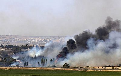 Smoke rises from a fire as a result of fighting in the the Syrian village of Quneitra near the border with Israel, as seen from an observatory near the Quneitra crossing, Thursday, June 6, 2013 (photo credit: AP/Sebastian Scheiner)