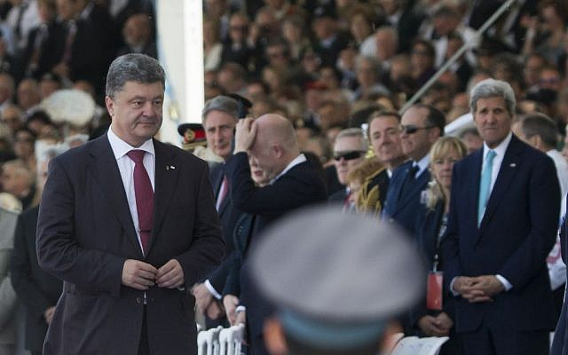 Ukraine's President-elect Petro Poroshenko left, walks past US Secretary of State John Kerry, right, at the commemoration of the 70th anniversary of the D-Day in Ouistreham, western France, Friday, June 6, 2014.  (Photo credit: AP Photo/Alexander Zemlianichenko)