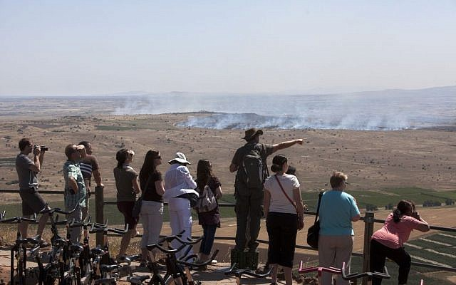 Israelis and tourists look at smoke from fires caused by fighting in Syria from an observation point on Mt. Bental in the Golan Heights, June 7, 2013 (photo credit: AP/Sebastian Scheiner)