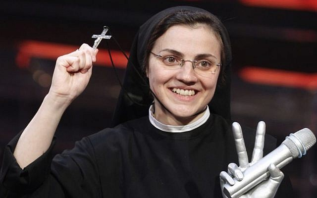 """Sister Cristina Scuccia poses with the trophy and holding the cross on the stage after winning the final of the Italian version of the TV talent show """"The Voice"""" in Milan, Italy, Thursday, June 5, 2014. With her full habit, sensible shoes and cheering nuns in her camp, Sister Cristina Scuccia made it to Thursday's finals of the Italian version of """"The Voice"""" after capturing attention, and millions of YouTube viewers, with her first-round performance in March. (AP Photo/Luca Bruno)"""