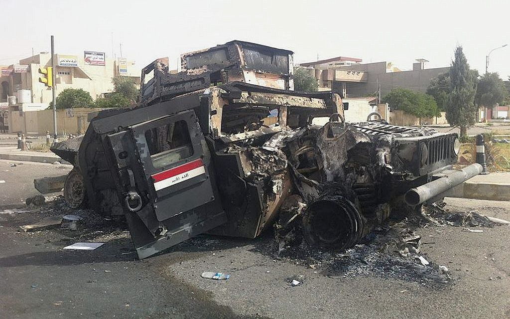 An Iraqi army armored vehicle is seen burned on a street of the northern city of Mosul, Iraq, Thursday, June 12, 2014 (photo credit: AP)