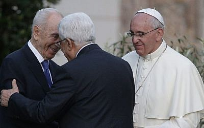 Pope Francis looks on as Israel's then-president Shimon Peres (left), and Palestinian Authority President Mahmoud Abbas greet each other during an evening of peace prayers in the Vatican gardens, Sunday, June 8, 2014. (photo credit: AP/Gregorio Borgia)