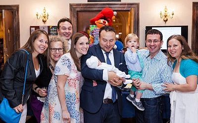 Seth Galena and Hindy Poupko, on his right shoulder, celebrate the birth of their son Akiva at his bris, June 15, 2014. (Piha Studio/via JTA)