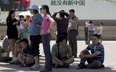 """Chinese visitors gather underneath a shadow from a lamp post near a giant electronic screen showing Chinese government propaganda song lyrics reading """"Without Communist Party, there is no new China"""" at Tiananmen Square in Beijing, China, on May 28, 2014. (photo credit: AP Photo/Andy Wong)"""