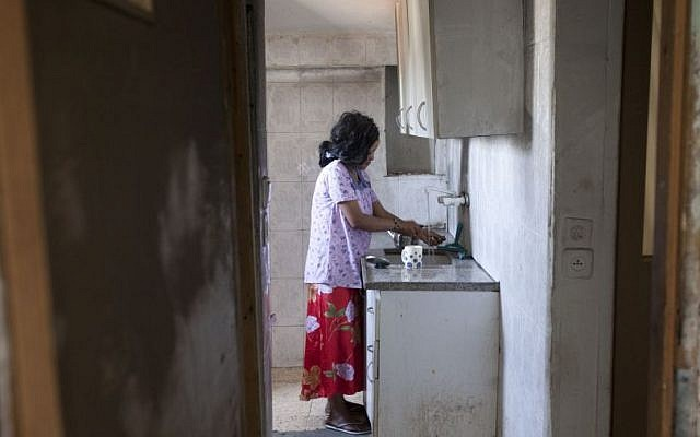 An African migrant from Eritrea is seen in her Jerusalem apartment after unknown attackers set it ablaze, June 2012. (photo credit: Yonatan Sindel/Flash90)
