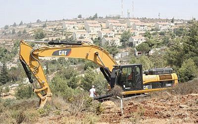 A Caterpillar tractor clearing land for Israeli homes in the West Bank, in 2012 (Oren Nahshon/Flash90)