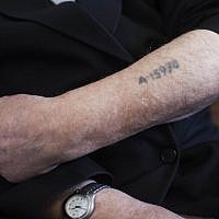 A Holocaust survivor shows his prisoner number tattooed on his arm. (Yonatan Sindel/Flash90)