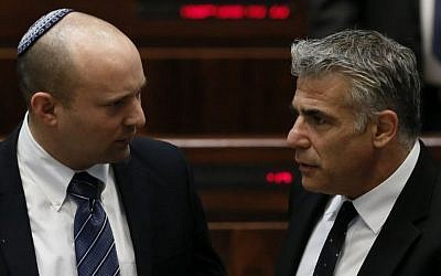 Then-Economy Minister Naftali Bennett (left) with then-finance Minister Yair Lapid in the Knesset, March 11, 2014. (Miriam Alster/Flash90)