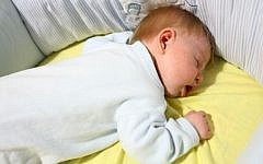 A baby seen sleeping in a cradle, illustrative photo (Photo credit: Chen Leopold/Flash90)