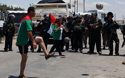 Illustrative photo of Palestinians playing soccer while rallying for hunger-striking prisoners outside Ofer Prison in the West Bank, on June 11, 2014. (Issam Rimawi/Flash90)