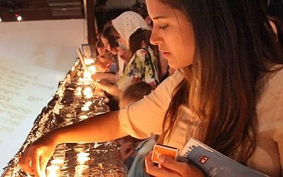 """A young woman lights the Shabbat candles during preparation for setting a Guinness World record of the largest Shabbat dinner in the world, organized by """"White City Shabbat"""" and held at the Tel Aviv port on June 13, 2014.  (Photo credit: Gideon Markowicz/FLASH90)"""