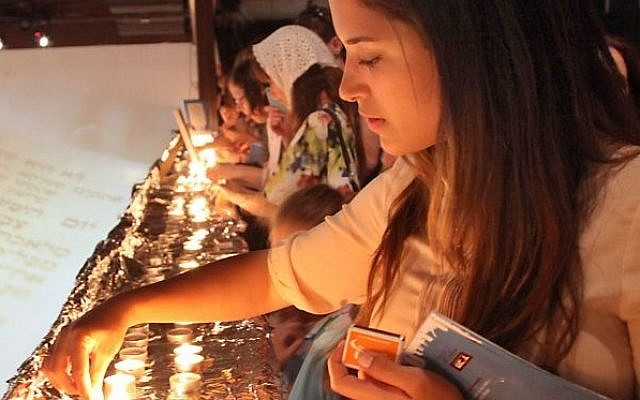 "A young woman lights the Shabbat candles during preparation for setting a Guinness World record of the largest Shabbat dinner in the world, organized by ""White City Shabbat"" and held at the Tel Aviv port on June 13, 2014.  (Photo credit: Gideon Markowicz/FLASH90)"