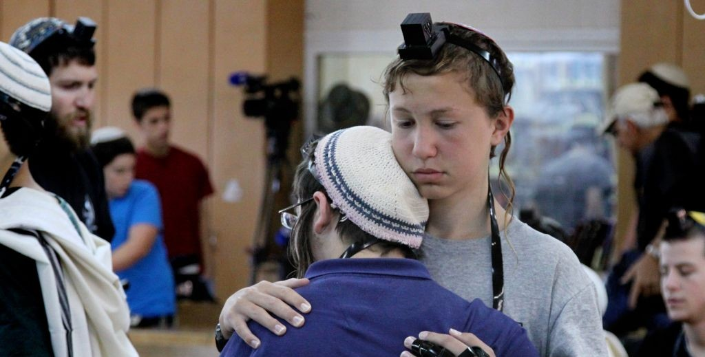 Students at the Mekor Haim Yeshiva comfort each other during a prayer session Sunday for three kidnapped teens. (Photo credit: Gershon Elinson/FLASH90)