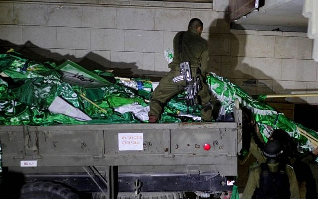 Israeli soldiers seen loading Hamas flags onto an army truck during a patrol at Birzeit University, on the outskirts of the city of Ramallah in the West Bank, during an operation on June 19, 2014. (photo credit: Issam Rimawi/Flash 90)
