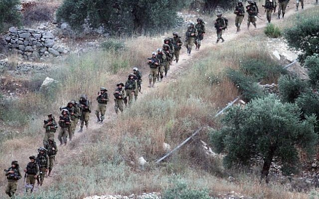 IDF soldiers patrol on the West Bank village of Aroura near Ramallah, early on June 20, 2014. (Photo credit:  Issam Rimawi/Flash 90)