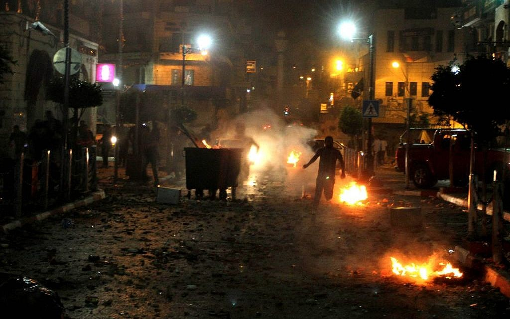 Palestinians during clashes with Israeli security forces taking part in the search for three missing teenagers early on June 22, 2014, in the West Bank city of Ramallah (photo credit: Issam Rimawi/Flash90)